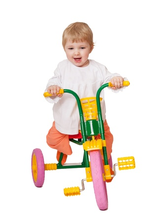 Happyl baby girl rides tricycle - studio shot; isolated on white photo