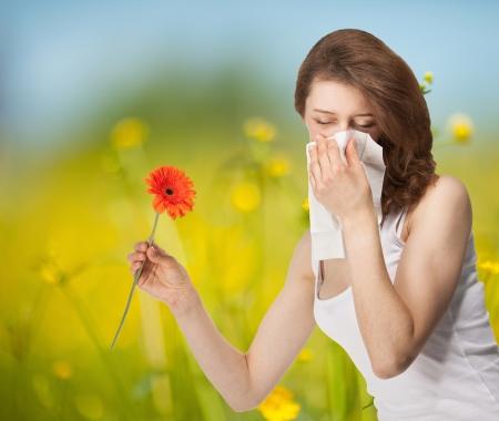 Jonge vrouw met allergie verblijft buiten in een zomer weide met rode Herber Stockfoto