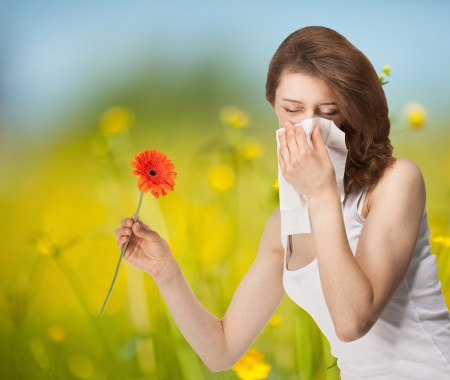 Young woman having allergy staying outdoors in a summer meadow with red herber