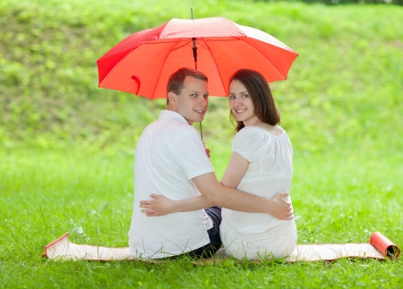 Happy smiling young couple sitting under red umbrella on a green summer meadow photo