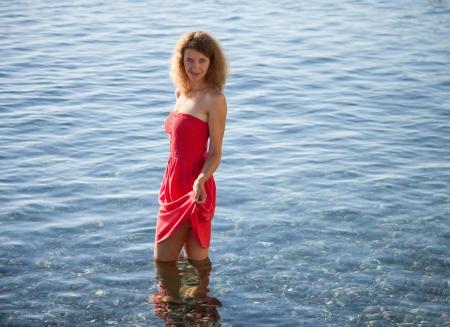 limpid: Smiling girl walking near the seashore in limpid water