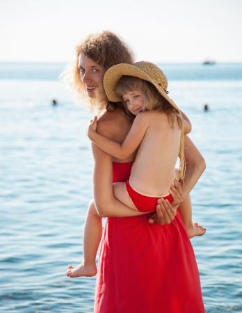 limpid: Happy mother and daughter walking near the seashore in limpid water