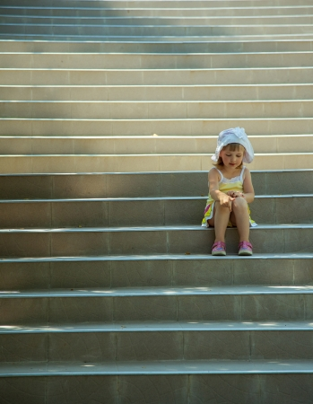 Cute little girl sitting on the stairs photo