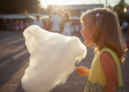 algodon de azucar: Ni�a encantadora comiendo algod�n de az�car