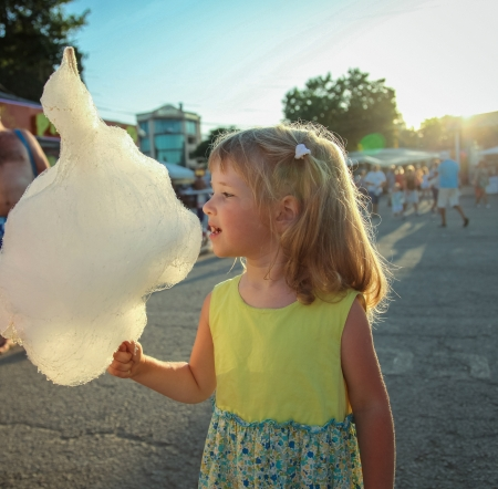 Charming little girl eating cotton candy photo