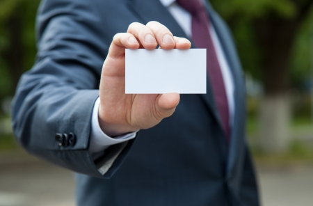 show business: Businessman showing blank business card standing outdoors in a park Stock Photo