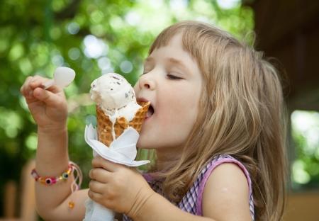jolie petite fille: Jolie petite fille mangeant une cr�me glac�e � l'ext�rieur