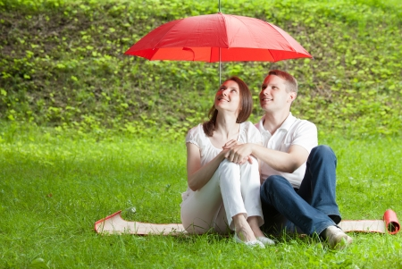 Beautiful young couple in love sitting on green summer meadow under red umbrella photo