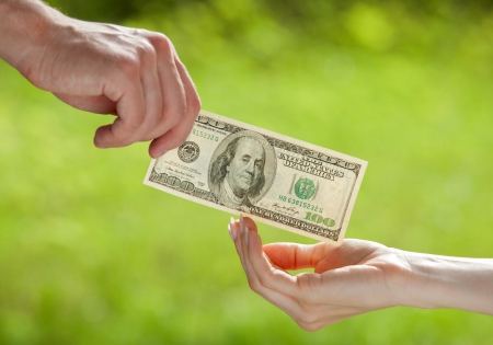 Hand proposing dollar banknote to the other hand, light green background photo