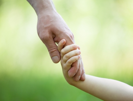 Hands of man and child holding together on light green background Foto de archivo
