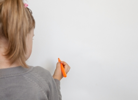 four p: Little girl drawing on a whiteboard Stock Photo