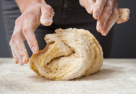 goods: Womans hands knead dough on a table