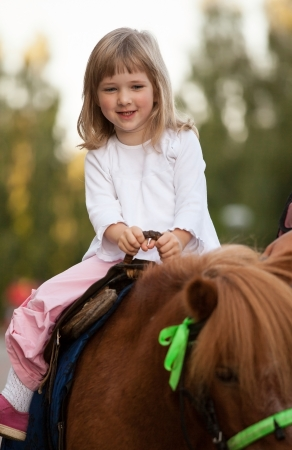 Gelukkig lachend meisje op een pony