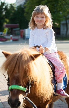 small children: Happy smiling little girl  on a pony Stock Photo