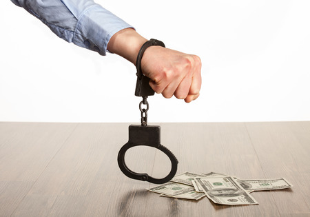 Hands in handcuffs and money  on the table; white background photo