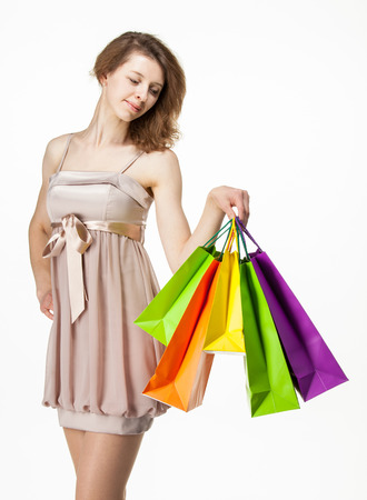 Attractive girl holding multicolored shopping paper bags - closeup shot on white background Stock Photo - 22752659
