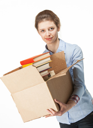 Smiling woman carrying a cardboard box with books, white background photo