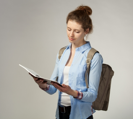 Pretty girl holding a notebook on grey background photo