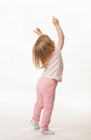 Weinig baby meisje blijkt iets boven haar, achteraanzicht; witte achtergrond