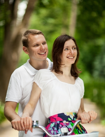 Beautiful happy young couple on bicycle in a summer park photo