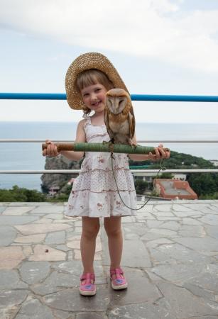 tame: Ni�a bonita que sostiene un palo con que se sientan al aire libre b�ho mansos