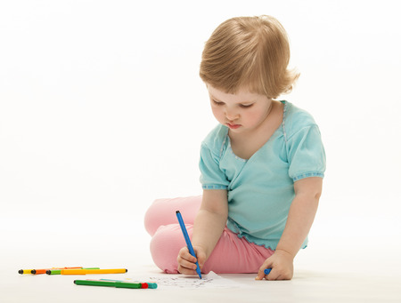 Child drawing a picture with colorful felt-tip pens; white background photo