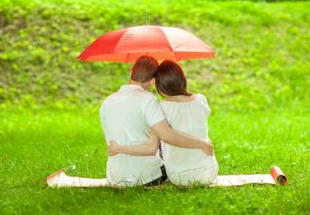 Couple in love sitting on green summer meadow under red umbrella embracing each other photo