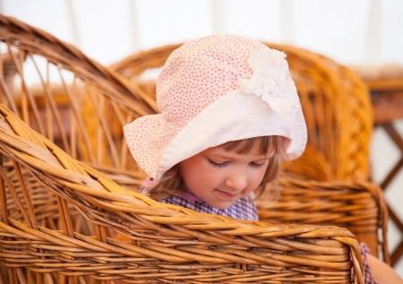 modest: Modest little girl sitting in a wicker chair