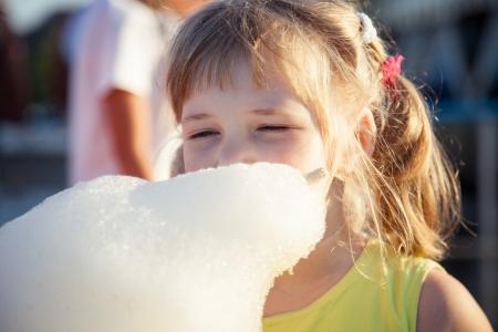 algodon de azucar: Funny niña comiendo algodón de azúcar