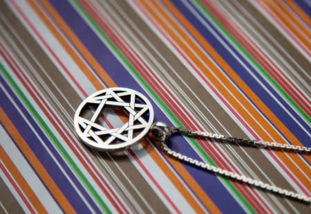 coulomb: Silver symbol of enneagramma on a color background