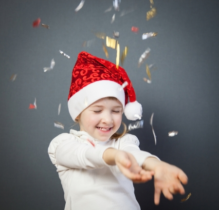 Portrait of a charming little girl in Santas hat, grey background photo