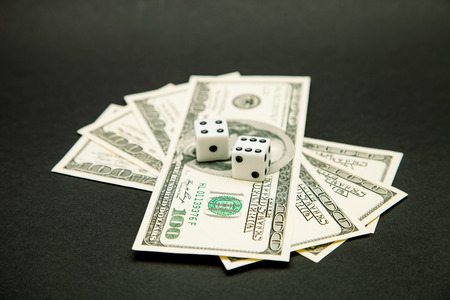 American dollars and dice on a dark table photo