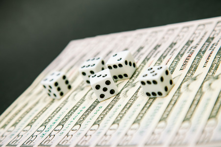 American dollars and dice on dark table photo