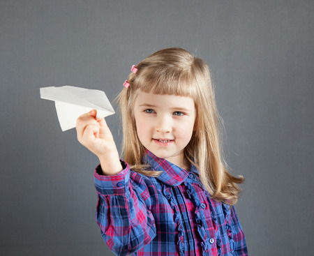 Smiling little girl flying paper plane on grey background photo