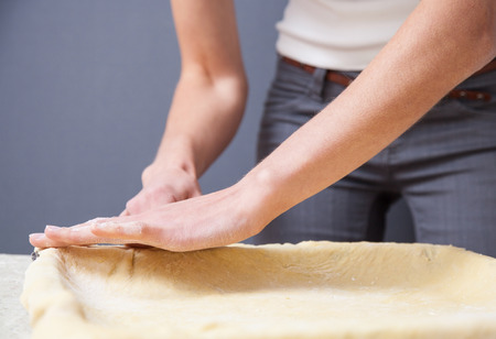 Woman's hands stretching dough on dark background photo