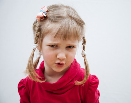 Portrait of a frowning little girl on neutral background Stock Photo
