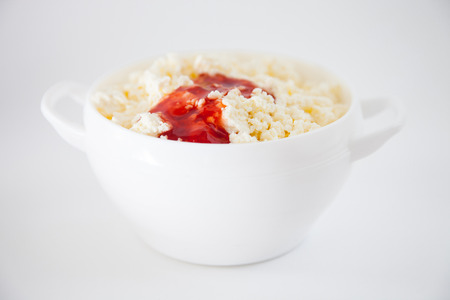 Cottage cheese with sweet jam in a white bowl photo