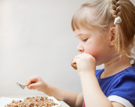 Adorable baby girl eating porridge; healthy eating for a child photo