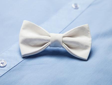 mo�o blanco: Pajarita blanca en una camisa azul de fondo Foto de archivo