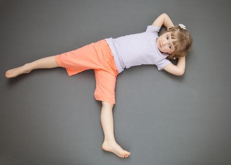 piedi nudi di bambine: Sorridente ragazza sdraiata sul pavimento, sfondo grigio Archivio Fotografico