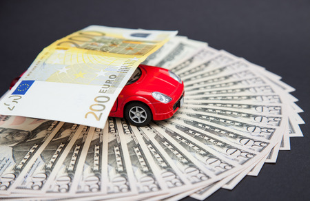 Small car carrying an euro banknote, grey background photo