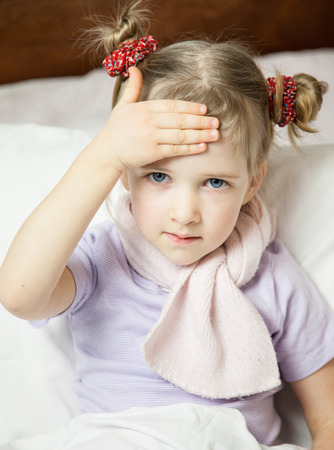 convalesce: Little girl touching her forehead - closeup portrait Stock Photo