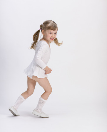 Active little girl training on white background photo