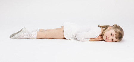 Beautiful little girl resting on the floor, white background photo
