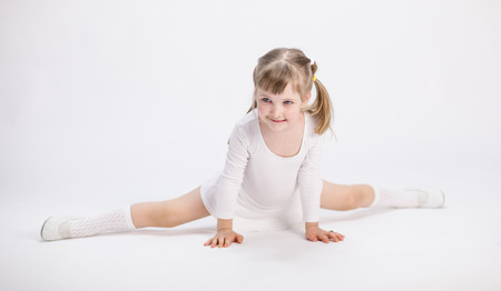 Smiling little girl doing the splits on white background photo