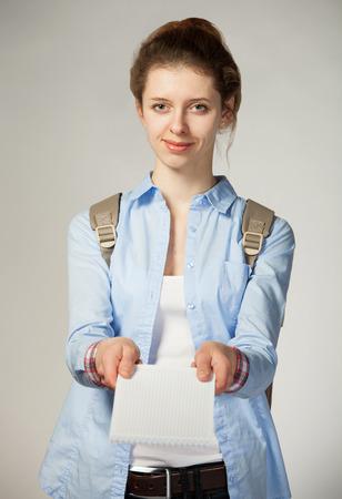 灰色背景: 魅力的な女の子の持株乳製品; 灰色の背景