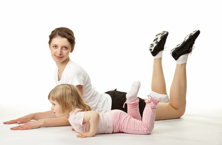 attractive young woman: Attractive young woman doing sport exercises with her little daughter on white background