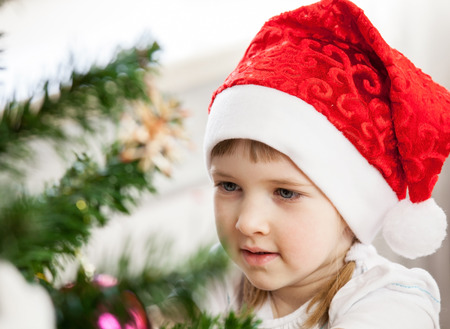 decorates: Beautiful little girl decorates the Christmas tree