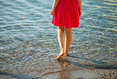 limpid: Unrecognizable slender girl walking near the seashore in limpid water Stock Photo