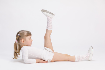 Pretty little girl lying on the floor and doing exercise, white background